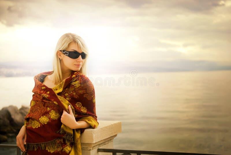 nära havsolnedgångkvinna arkivfoto