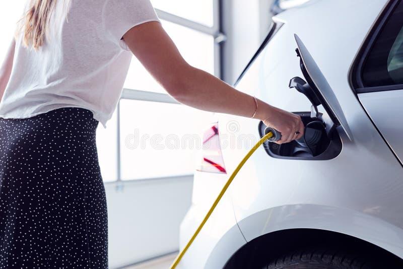 Nära laddande elfordon för kvinnor med kabel i garaget i hemmet royaltyfri fotografi