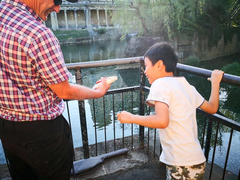Nära London Thames River och den Putney bron fiskade en gamal man, hålla ögonen på för barn royaltyfria foton