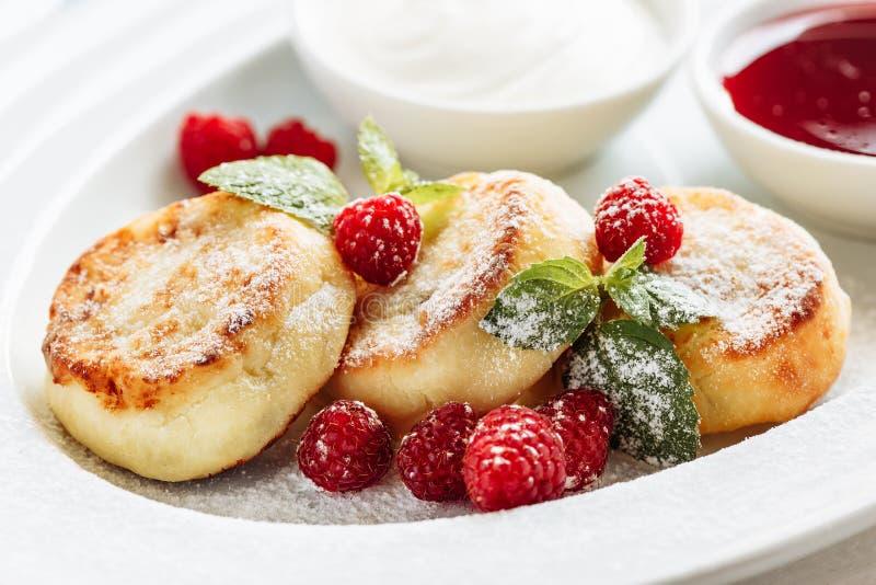 Nära ostpannkakor, syrniki, ostmassastruvor med nya hallon på vit plattabakgrund royaltyfria foton