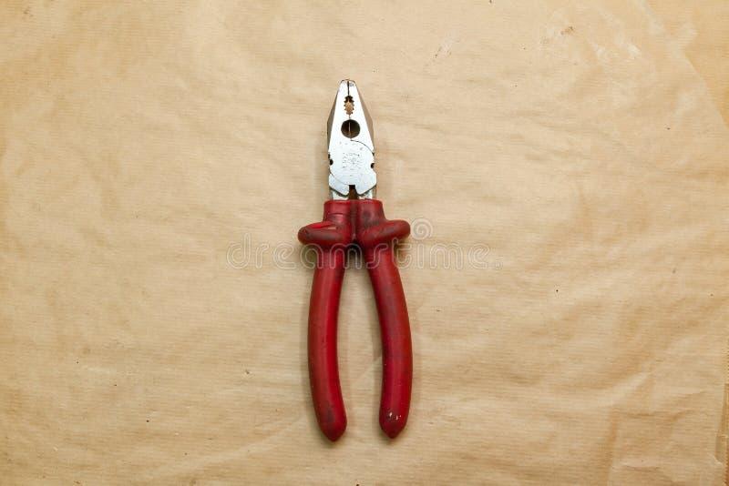 Nära plattång med röda gummihandtag som används under arbete för att klämma fast delar för hantverk i hjälpmedelseminarie royaltyfri fotografi