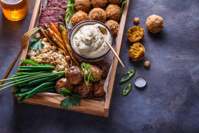 Nära sikt av blandat mezeaptitretarenötkött, falafel, babaghanoush, potatisar i en ask, copyspace fotografering för bildbyråer