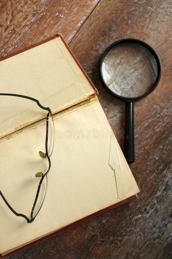 Nära sikt av den läsningexponeringsglas och förstoringsapparaten på den stora antika boken royaltyfri fotografi