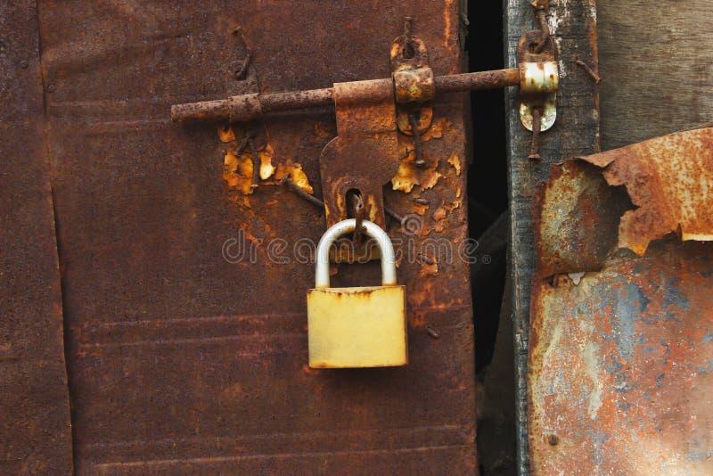Nära sikt av den rostade dörren med låset arkivbilder