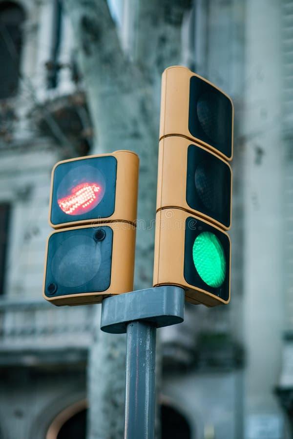Nära sikt av en grön trafikljus och fot- bruten röd trafikljus som är röda med suddig bakgrund arkivfoto