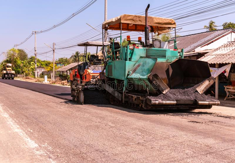 Nära sikt på arbetarna och de asfaltera maskinerna, arbetare som gör asfalt på vägkonstruktion arkivfoto