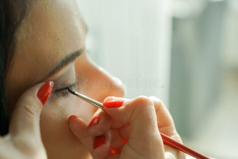 Nära sikt på framsidan av kvinnan som har en makeup arkivfoto