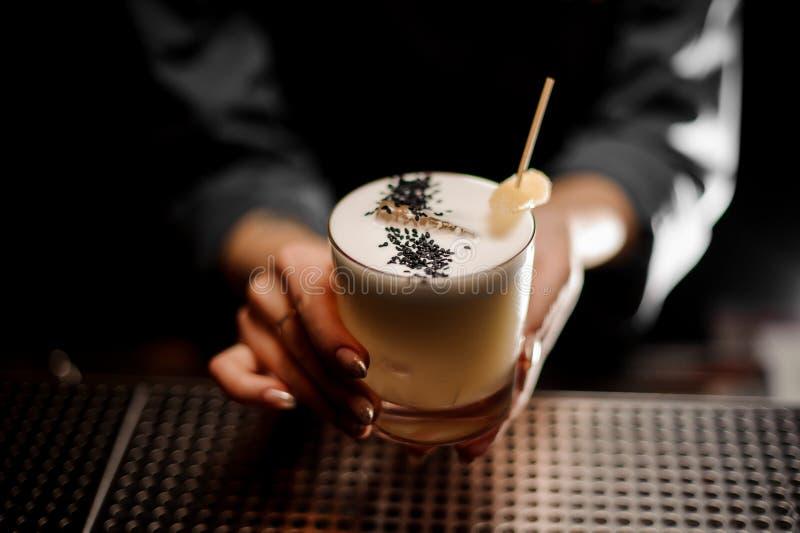 Nära skott av en alkoholcoctail i bartenders händer arkivfoton