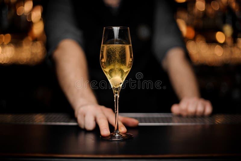 Nära skott av exponeringsglas med mousserande vin i bartenderns händer arkivfoton