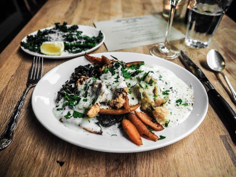 Nära skott av stekte morötter och att mosa potatisar med kött och special sås på en rund vit platta arkivfoto