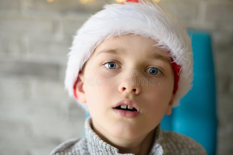 Nära stående av 8 år pojke i den Santa Claus hatten arkivfoton