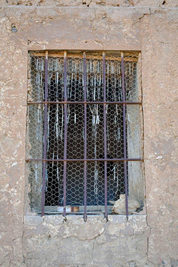 nära upp av ett gammalt träfönster med stänger av järn som blockerar tillträde, i en vägg av betong, gyttja och stenen i övergett royaltyfri bild