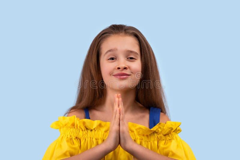 Nära upp emotionell stående av den unga blonda flickan som bär gula sundress på blå bakgrund i studio Hon tigger för något arkivfoto