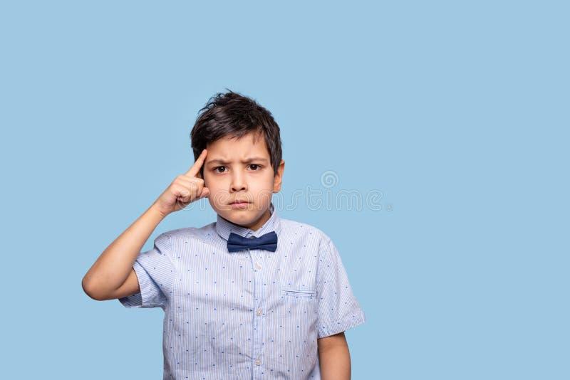 N?ra upp emotionell st?ende av en allvarlig pojke som t?nker av n?got Han rymmer hans pekfinger p? templet som visar denna gest arkivfoto