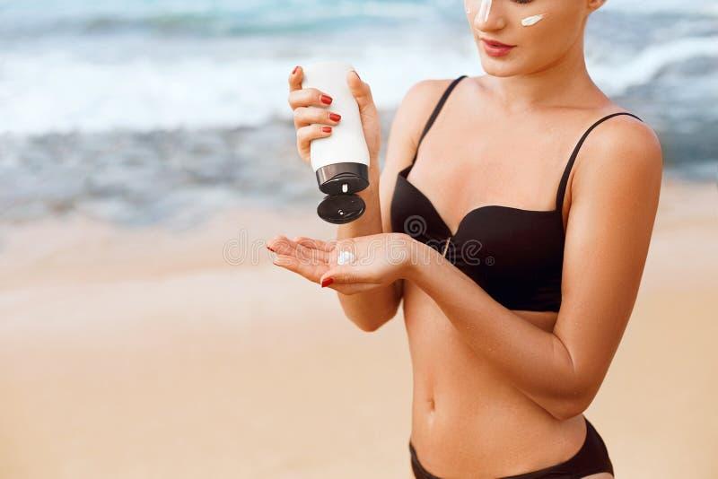 Nära upp härlig kvinna i bikinin som applicerar solkräm på händer Kvinna som s?tter sol- kr?m p? skuldra n?ra p?len applicera gen arkivbild