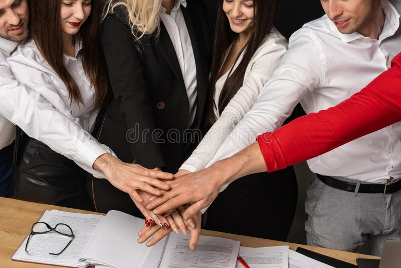 Nära upp kantjusterad stående av positiva businesspeople som tillsammans sätter armar arkivbild