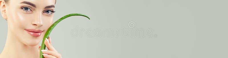 Nära upp kvinnlig framsida med aloe Härlig modell med sund klar hud och det aloevera bladet på banerbakgrund arkivbilder
