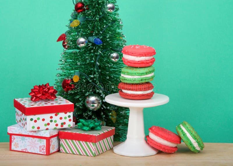 Nära upp på macaronkakor bredvid julgranen med gåvor royaltyfri bild