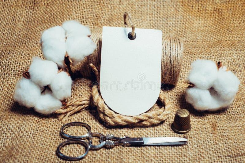 Nära upp pappers- etikett med repfingerborg, sax på tappningtyger bredvid bomullsbollar Falsk övre bomullsmall arkivfoton