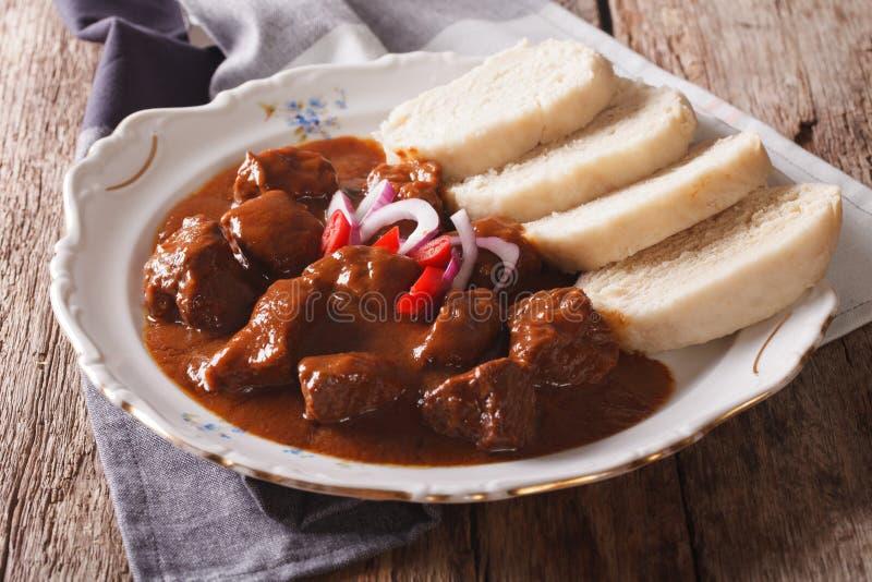 Närande gulasch med kokta Knodel på en plattanärbild Horiz arkivfoto