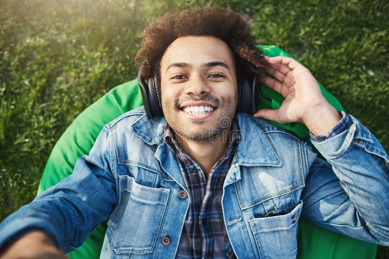 Närbildövresiktsskott av den stiliga afrikanska mannen med den fördjupande handen för afro frisyr in mot kamera medan lyssnande m arkivbilder