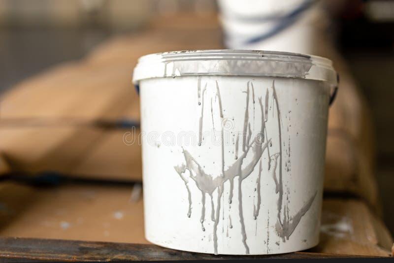 Närbild använd smutsig plast- målarfärghink för vit i rum Renovering- och reparationsprocessbegrepp Copyspace produkt royaltyfri bild