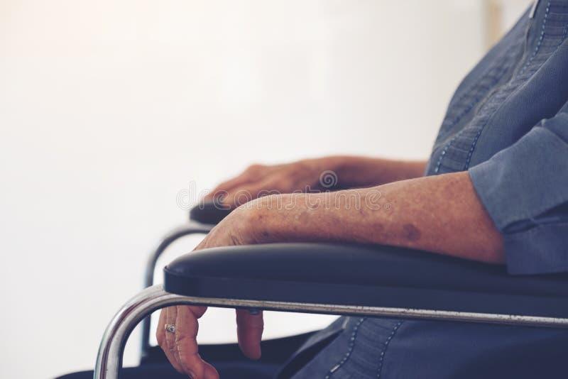 Närbild av äldre händer för kvinna` s på rullstolen, Thailand royaltyfri foto