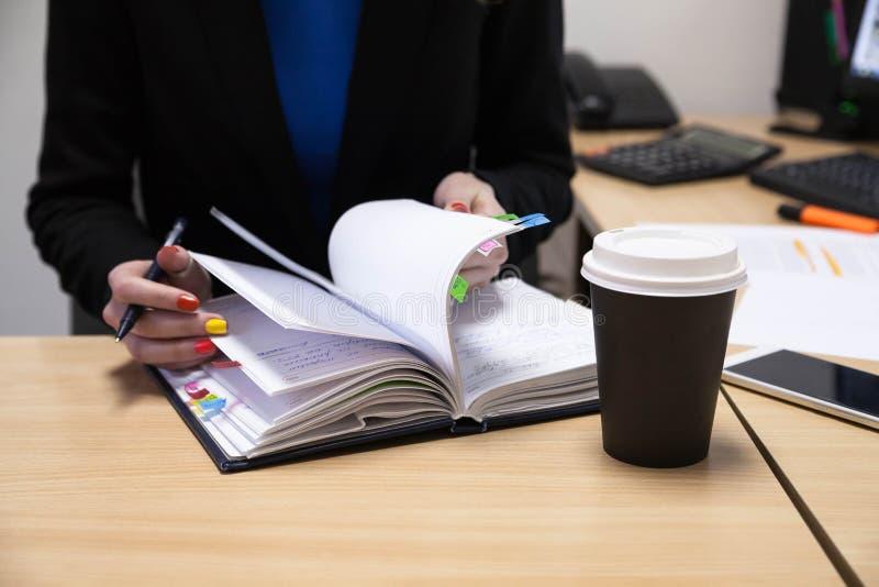 Närbild av affärskvinnaMaking Agenda On en personlig organisatör At Workplace arkivfoton