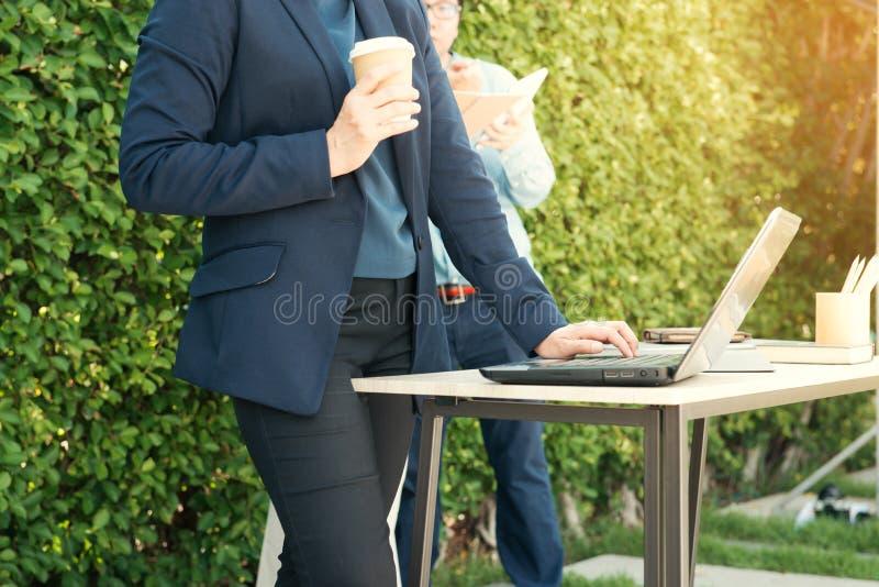 Närbild av affärskvinnamaskinskrivningdokument på tangentbordet av bärbar datorhållkoppen kaffe och affärsfolk som arbetar på bak arkivbild
