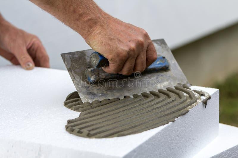 Närbild av arbetarhanden med mursleven som applicerar lim på det vita styva arket för polyuretanskum för husisolering Modern tekn royaltyfri bild