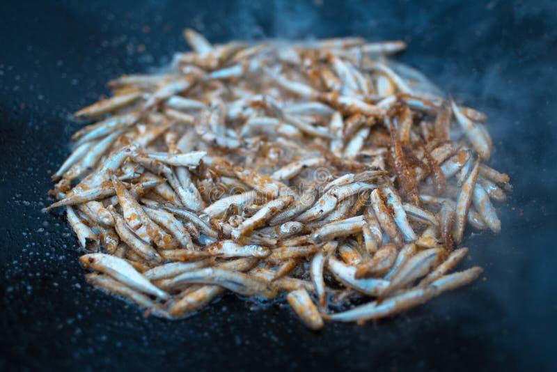 Närbild av att laga mat fisken i plan panna på brasa royaltyfri foto