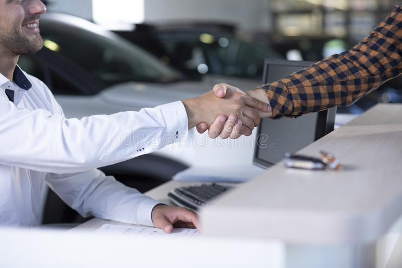 Närbild av att le bilsäljaren som skakar handen för köpare` s efter transa arkivfoto