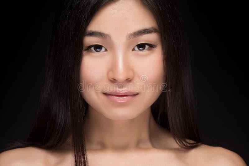 Närbild av att le den asiatiska kvinnan i studio arkivfoto