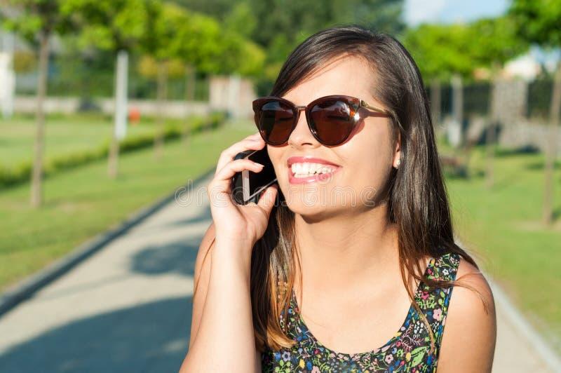 Närbild av att le den attraktiva flickan som talar på telefonen royaltyfri bild