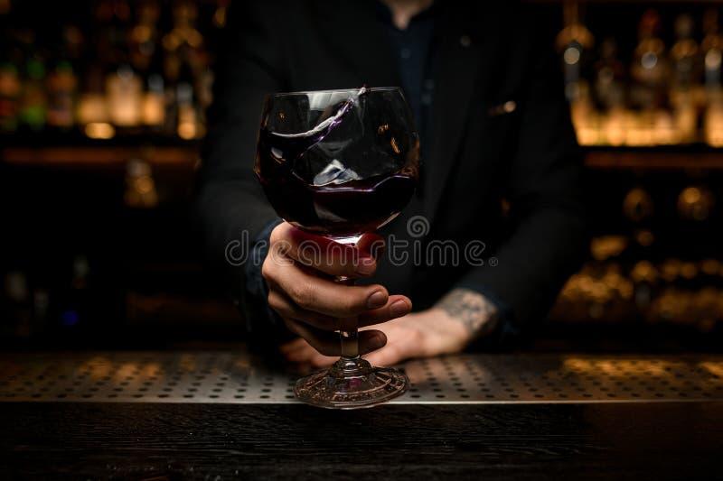 Närbild av att plaska alkoholcoctailen i bartenders händer royaltyfri foto