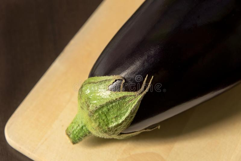 Närbild av aubergine, aubergine på skärbräda på mörk bakgrund arkivfoto
