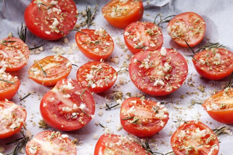 Närbild av bakplåten med kryddade tomater arkivbild