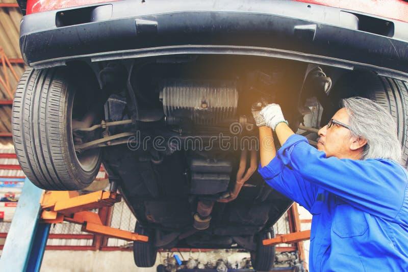 Närbild av bilmekanikern som arbetar under bilen i service för automatisk reparation royaltyfri foto