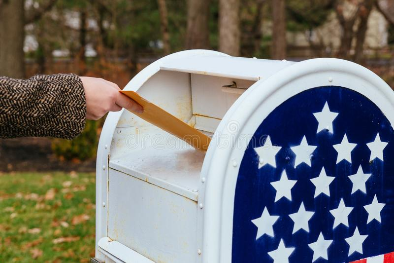 Närbild av brevbäraren som sätter bokstavsbrevlådaamerikanska flaggan arkivfoton