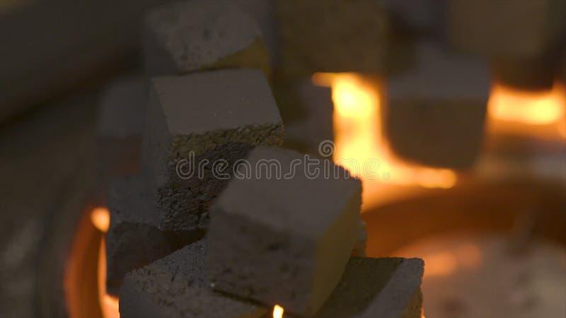 Närbild av brinnande kolkuber actinium Kuber av glöd som bränner i bunken för att röka vattenpipan Förbränning av litet arkivfoto