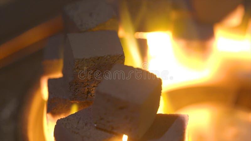Närbild av brinnande kolkuber actinium Kuber av glöd som bränner i bunken för att röka vattenpipan Förbränning av litet arkivbild