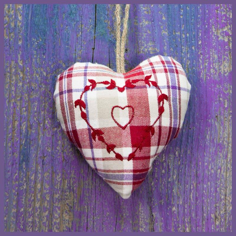 Närbild av broderad hjärtaform på purpurfärgad träyttersida. arkivbild