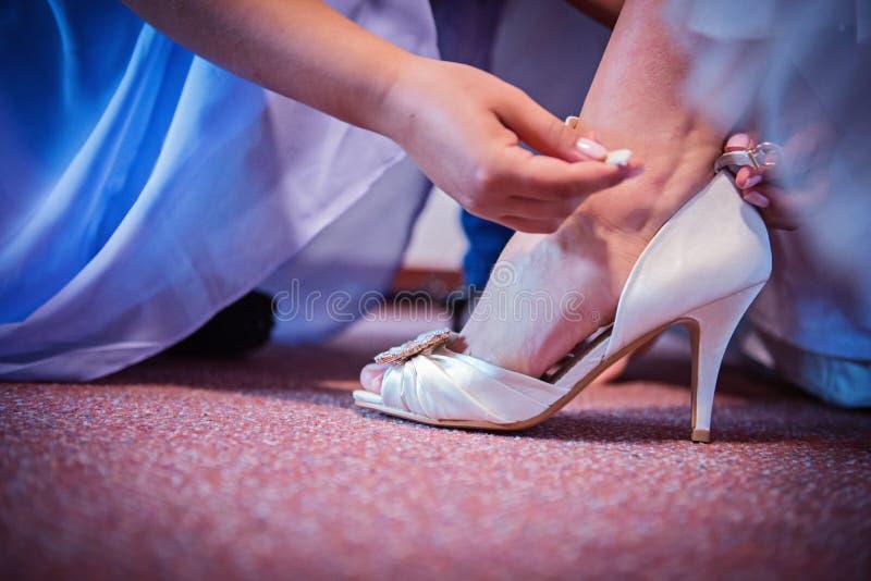 Närbild av bruden i den pålagda beigea bröllopsklänningen henne skor arkivfoto