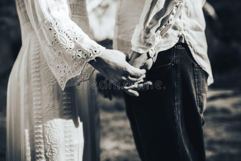 Närbild av brudgummen som rymmer bruden vid händerna royaltyfria foton