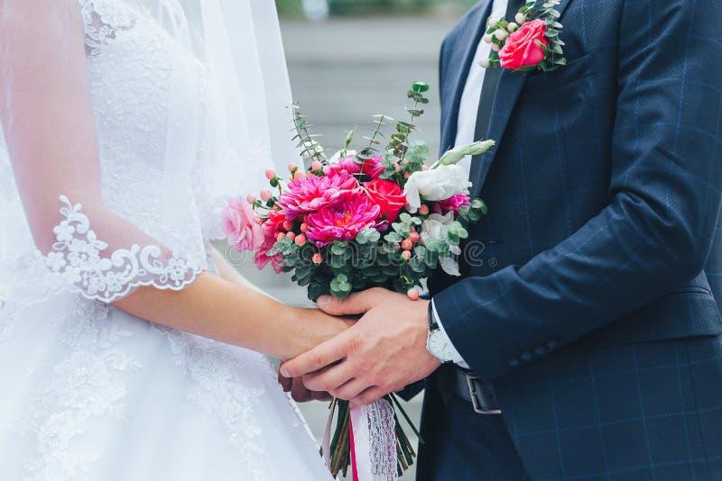 Närbild av brudgummen som rymmer bruden vid händerna arkivbild