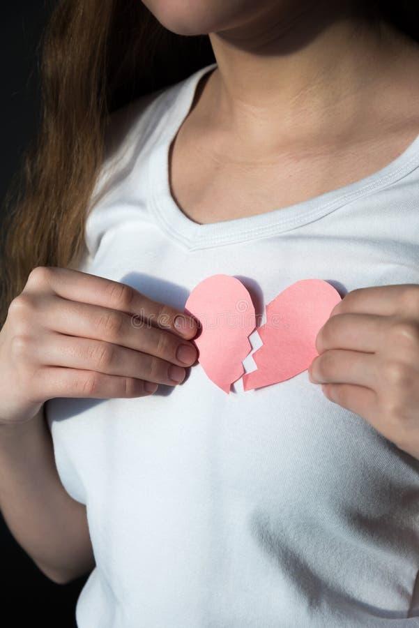Närbild av bruten hjärta som rymms mot kvinnas bröstkorg arkivbilder