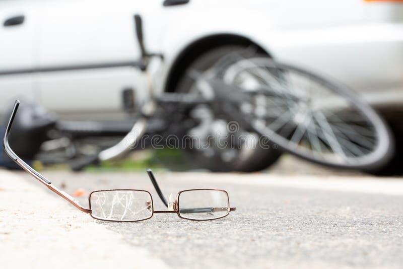 Närbild av brutna exponeringsglas på en väg med en suddig cykel och bil arkivbilder
