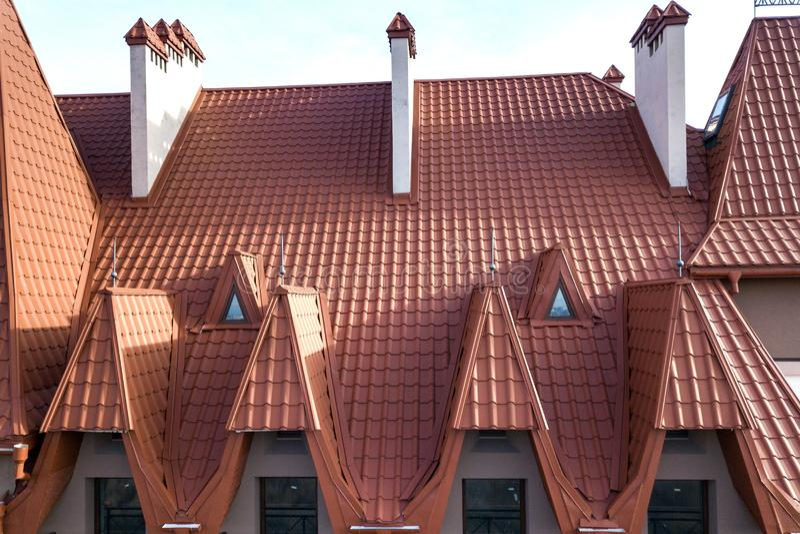 Närbild av byggande fasadyttersida med stuckaturväggen, gjutjärnbalkongräcke, det branta singeltaket och skinande fönster arkivfoton