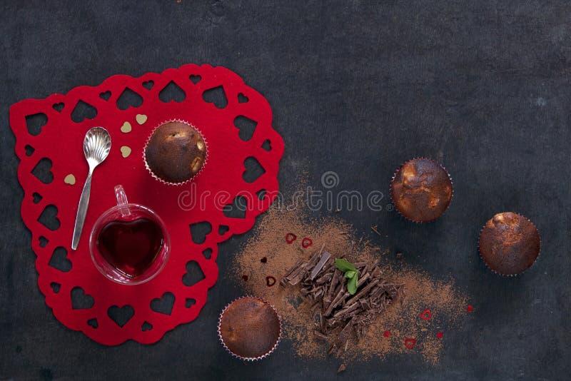 Närbild av chokladmuffin med sked- och tekoppen på rött hjärta-format bräde arkivbilder