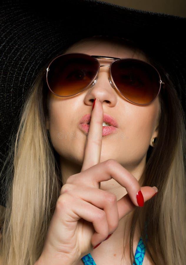 Närbild av den attraktiva brunettkvinnan i en bikini, en stor hatt och en solglasögon som sätter ett finger på hennes kanter fotografering för bildbyråer